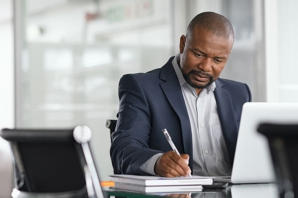 business-man-writing-summary-at-desk-with-pen