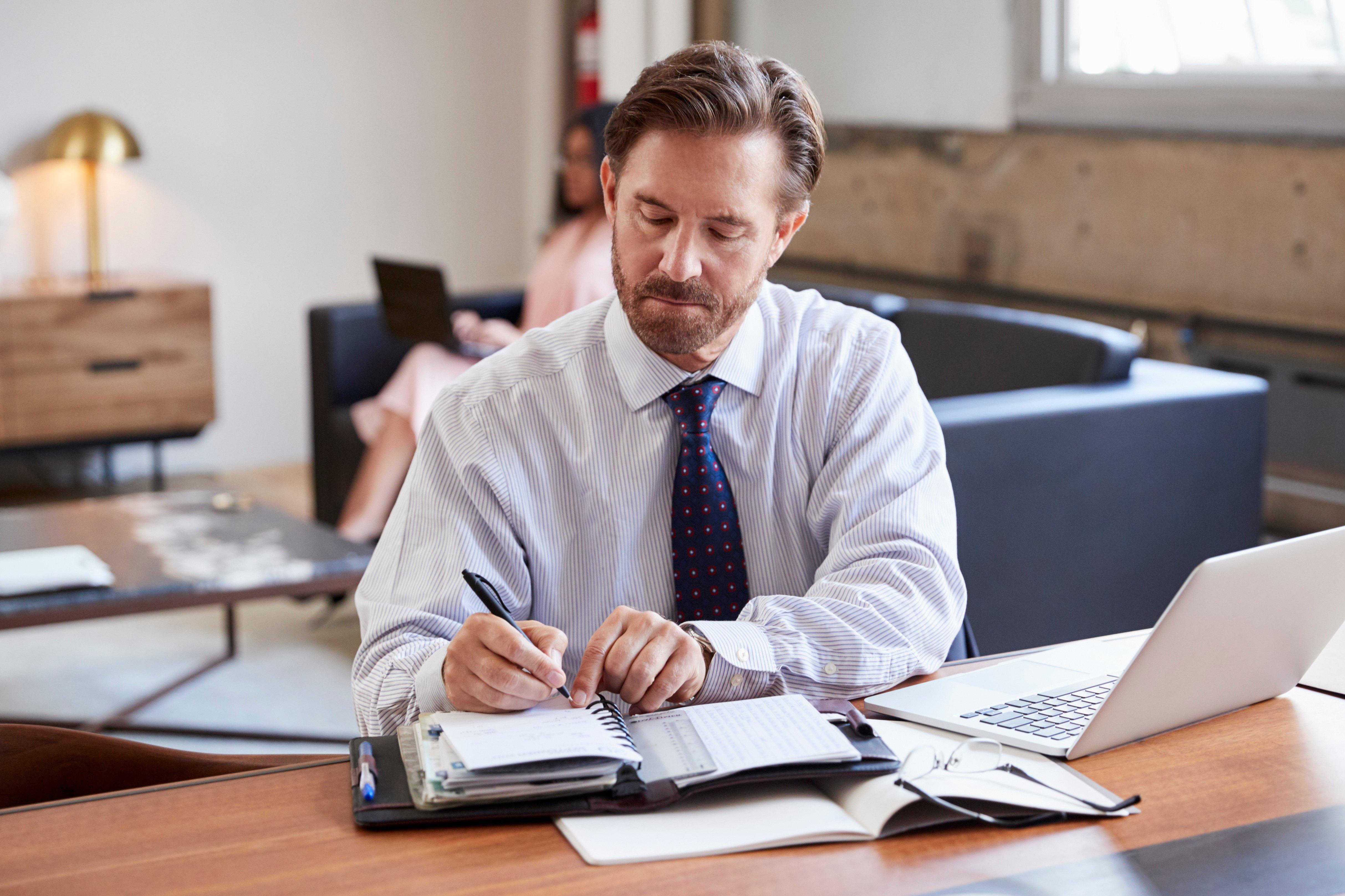 businessman-at-desk-writing-notes-P9ENRHD