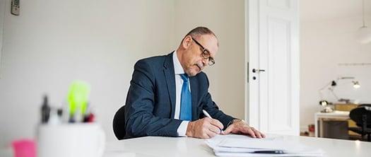 businessman-writing-summary-documents-at-desk